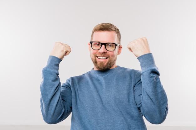 Giovane imprenditore di successo in pullover blu che esprime gioia mentre in piedi davanti alla telecamera in isolamento