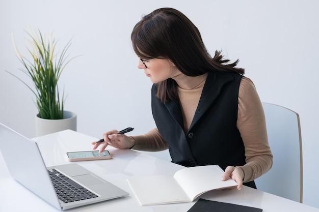Giovane imprenditrice di successo con quaderno aperto lo scorrimento nello smartphone mentre è seduto alla scrivania davanti al computer portatile