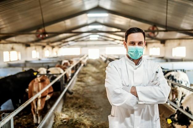 Giovane veterinario caucasico di successo in piedi nel fienile con le braccia incrociate