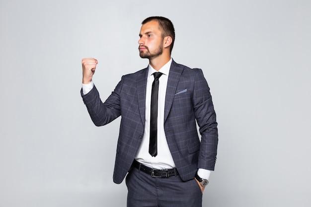 Giovane imprenditore felice di successo in abito formale urlando e stringendo i pugni isolate su uno sfondo grigio