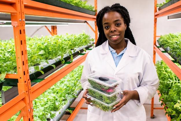 Giovane agronomo femminile di successo in whitecoat che tiene pila di contenitori di plastica con foglie verdi fresche