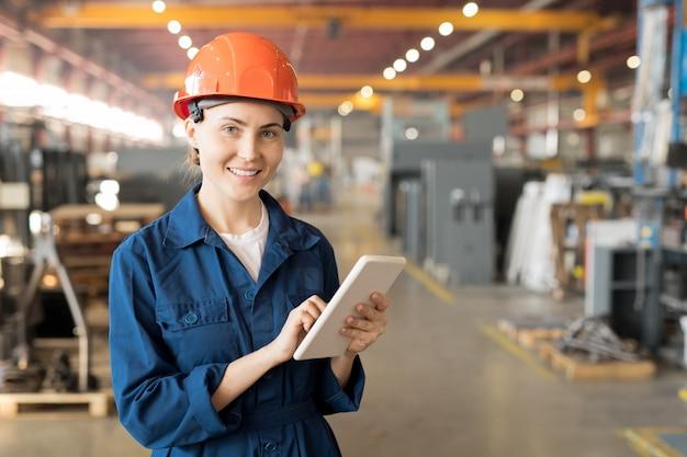 Giovane ingegnere femminile di successo di grande impianto industriale che naviga in rete
