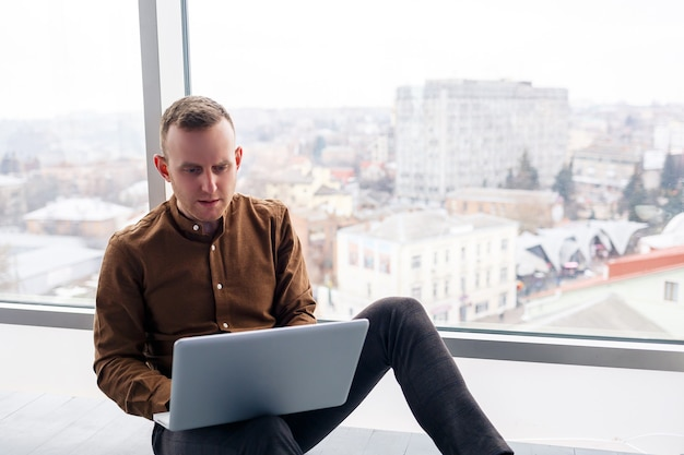Il giovane uomo d'affari maschio di successo si siede vicino a una grande finestra con un computer portatile. lavoro a distanza