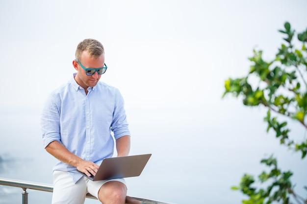 Giovane uomo d'affari maschio di successo che lavora con il computer portatile in vacanza al mare. indossa occhiali da sole, maglietta e pantaloncini bianchi. lavoro fuori ufficio, libero professionista
