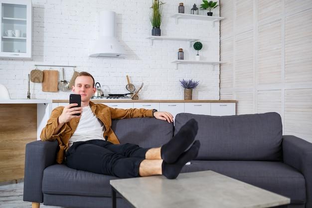 Un giovane uomo di successo è seduto a casa sul divano con un telefono e parla su un collegamento video. lavoro a distanza durante la quarantena.