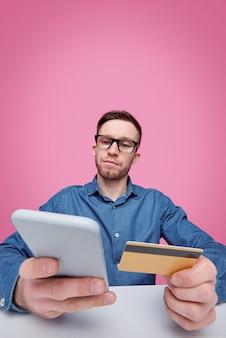 Giovane uomo di successo con carta di plastica e smartphone che scorre le merci mentre va a fare ordine nel negozio online