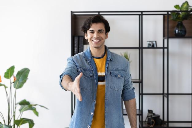 Il giovane uomo millenario di successo in abiti casual allunga la mano per il saluto della stretta di mano. l'imprenditore è in piedi in ufficio