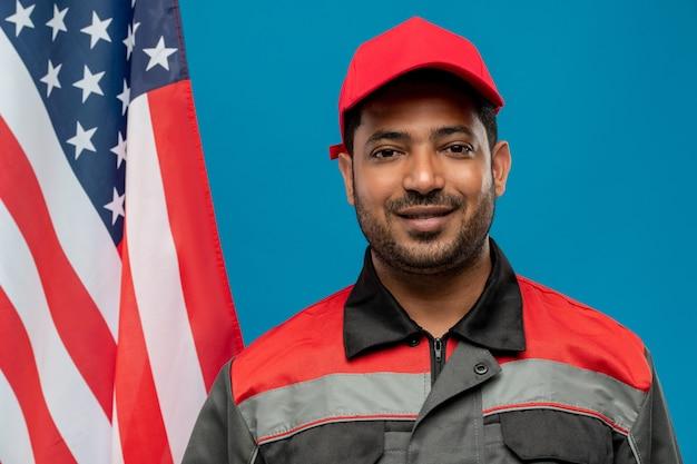 Giovane operaio o riparatore di razza mista di successo che ti guarda mentre in piedi davanti alla telecamera con la bandiera americana sul blu
