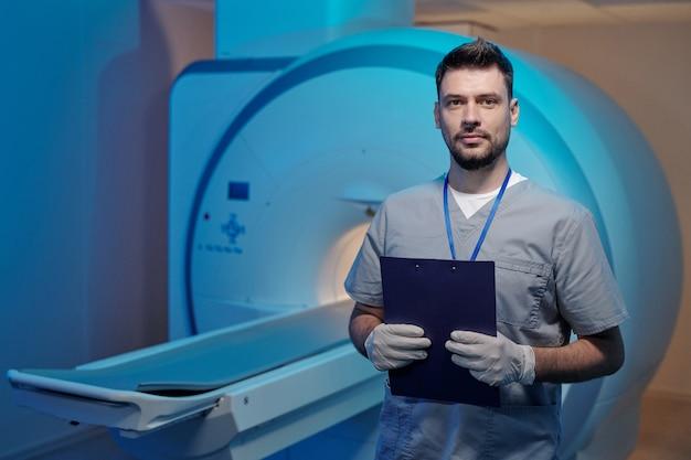 Giovane radiologo di successo con documento in piedi contro l'attrezzatura medica
