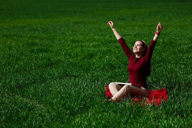 La giovane donna di successo è seduta sull'erba verde con un computer portatile in mano. riposa dopo una buona giornata di lavoro. lavora sulla natura. studentessa che lavora in un luogo appartato. nuove idee imprenditoriali