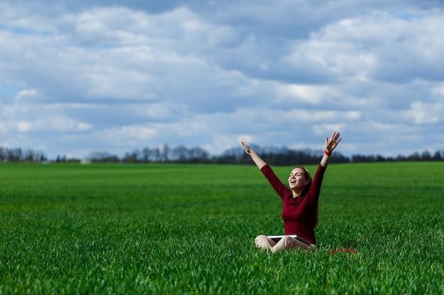 La giovane donna di successo è seduta sull'erba verde con un computer portatile in mano. riposa dopo una buona giornata di lavoro. lavora sulla natura. studentessa che lavora in un luogo appartato. posto di lavoro nella natura