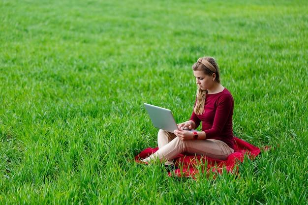 La giovane donna di successo è seduta sull'erba verde con un computer portatile in mano. lavora sulla natura. studentessa che lavora in un luogo appartato. nuove idee imprenditoriali