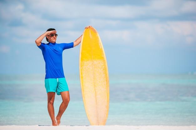 Giovane surfista in spiaggia bianca con tavola da surf gialla