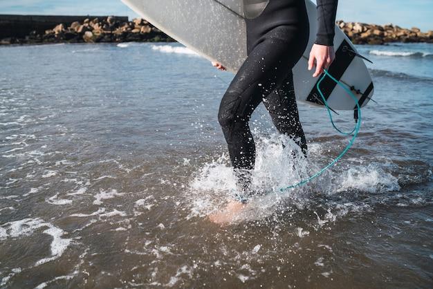 Giovane surfista che entra in acqua con la sua tavola da surf in un costume da surf nero. sport e sport acquatici concetto.