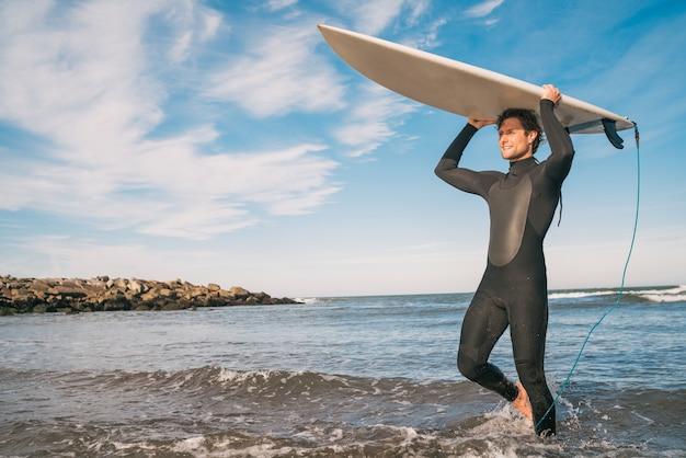 Giovane surfista che entra in acqua con la sua tavola da surf in un costume da surf nero