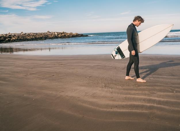 Giovane surfista in piedi nell'oceano con la sua tavola da surf in un costume da surf nero. sport e sport acquatici concetto.