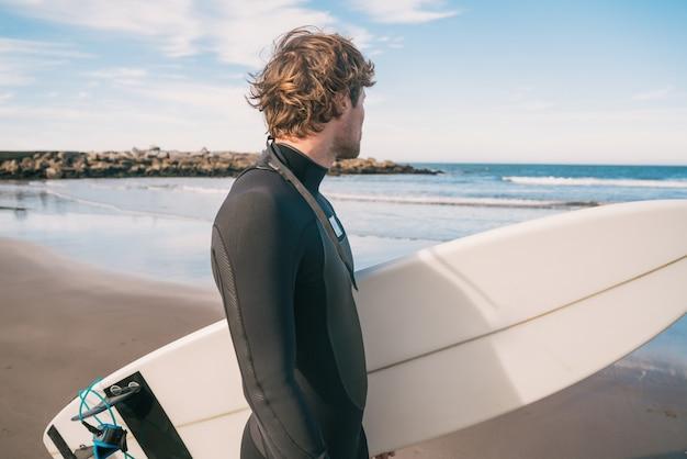 Giovane surfista in piedi nell'oceano con la sua tavola da surf in un costume da surf nero