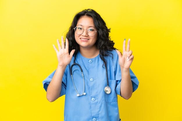Giovane chirurgo medico donna asiatica isolata su sfondo giallo contando otto con le dita