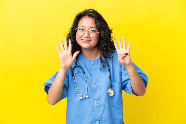 Giovane chirurgo medico donna asiatica isolata su sfondo giallo contando nove con le dita