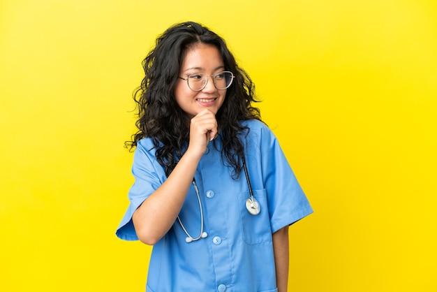 Giovane donna asiatica del medico del chirurgo isolata su fondo giallo che guarda al lato