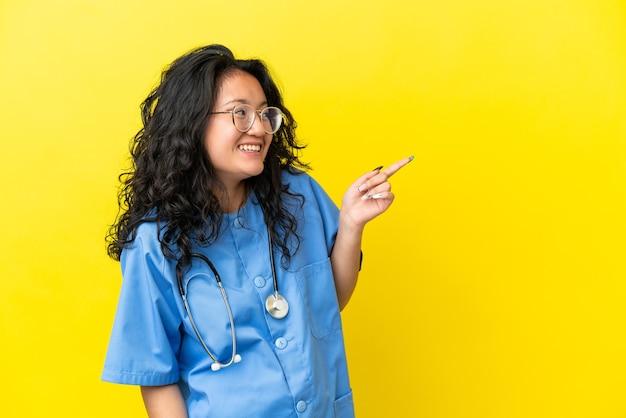 Giovane chirurgo medico donna asiatica isolata su sfondo giallo che punta il dito sul lato e presenta un prodotto