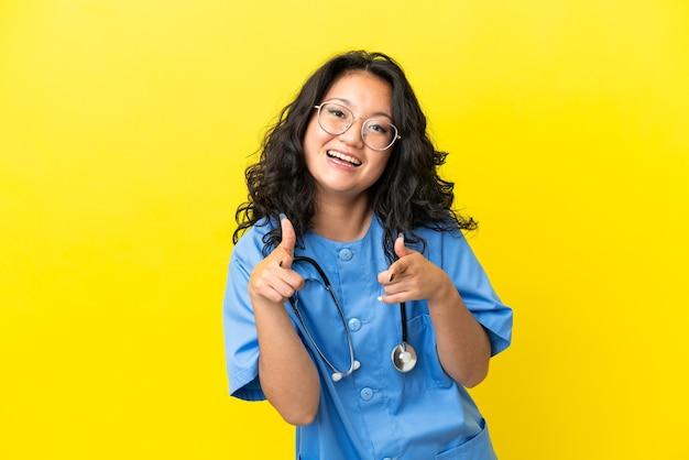 Giovane donna asiatica del medico chirurgo isolata su fondo giallo che indica la parte anteriore e che sorride