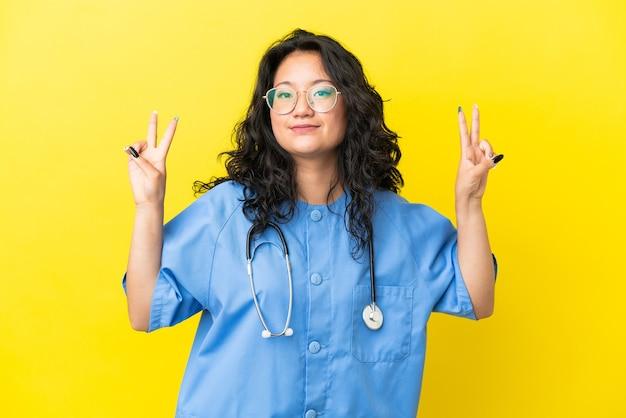 Giovane chirurgo medico donna asiatica isolata su sfondo giallo che mostra il segno di vittoria con entrambe le mani