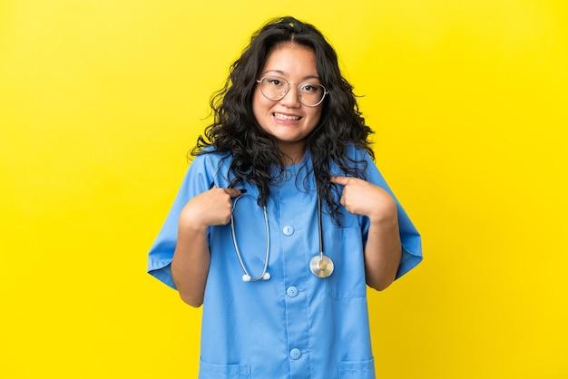 Giovane donna asiatica del medico del chirurgo isolata su fondo giallo con l'espressione facciale di sorpresa