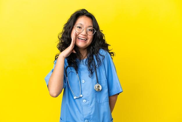 Giovane chirurgo medico donna asiatica isolata su sfondo giallo con espressione facciale sorpresa e scioccata