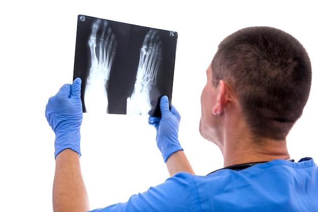 Giovane chirurgo esaminando un'immagine a raggi x del piede del paziente isolato su sfondo bianco.