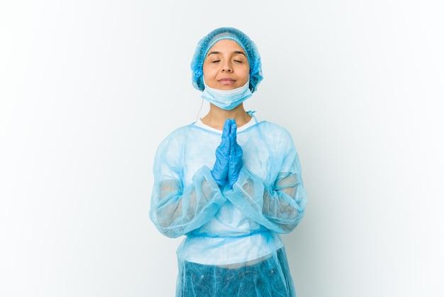 La giovane donna latina del chirurgo che tiene le mani nella preghiera vicino alla bocca, si sente sicura.