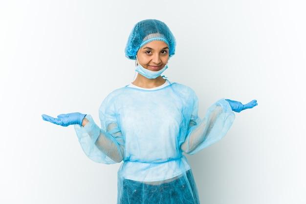 Giovane donna del chirurgo isolata sulla parete bianca che dubita e che scrolla le spalle le spalle nel gesto interrogativo