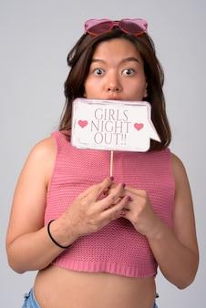 Giovane donna asiatica sorpresa con gli occhiali a forma di cuore pronti per la notte delle ragazze