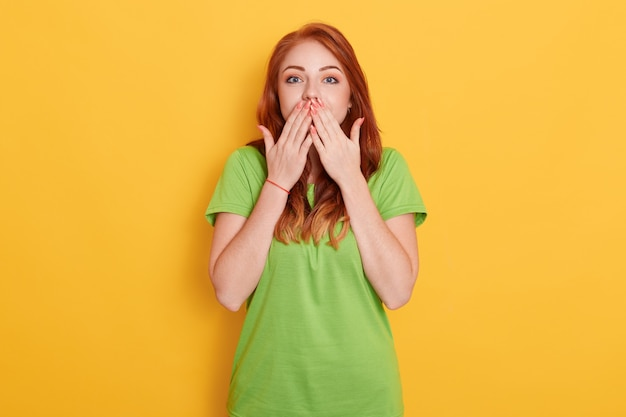 Giovane ragazza sorpresa stupita stupita che copre la bocca con due mani, sente notizie incredibili, bella donna con i capelli rossi su sfondo giallo.