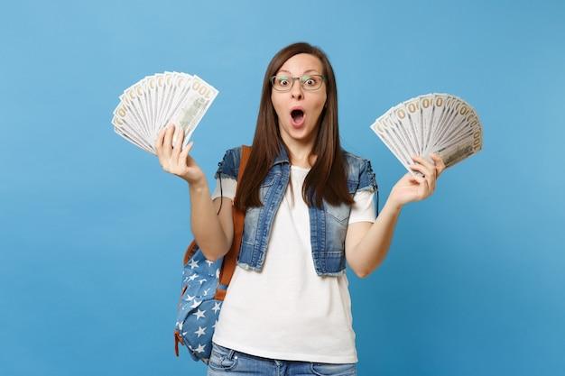 Giovane studentessa scioccata sorpresa con gli occhiali con lo zaino con la bocca aperta che tiene in mano un sacco di dollari, denaro contante isolato su sfondo blu. istruzione al college universitario di scuola superiore.