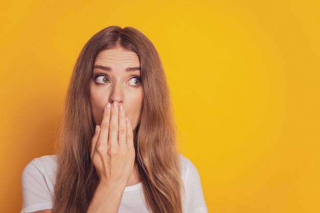 Giovane donna sorpresa che copre la bocca con la mano