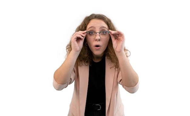 Giovane donna sorpresa che tiene i suoi occhiali con le mani. indossa un abito color corallo