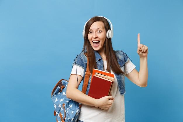 La giovane studentessa sorpresa con le cuffie dello zaino che ascolta la musica tiene il libro di scuola che indica il dito indice su sullo spazio della copia isolato su fondo blu. istruzione al college universitario di scuola superiore.