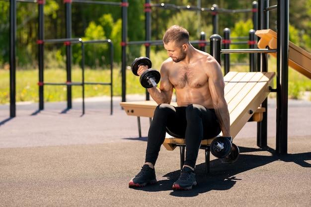 Giovane atleta muscoloso sudato seduto su impianti sportivi e allenandosi con manubri pesanti sul campo sportivo