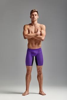 Giovane nuotatore in ottima forma fisica in piena crescita su uno sfondo grigio con spazio copia, invito allo sport, banner pubblicitario