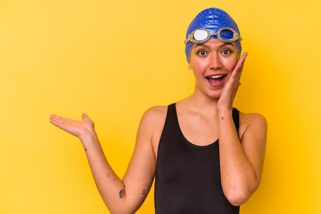 La giovane donna venezuelana nuotatrice isolata su sfondo giallo tiene lo spazio della copia su un palmo, tiene la mano sulla guancia. stupito e deliziato.