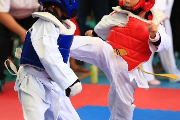 I giovani atleti di taekwondo stanno combattendo durante il concorso