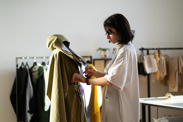 Il giovane sarto regola i dettagli del colletto al modello dei vestiti sul manichino con gli aghi nello studio di moda