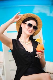 Modello giovane abbronzatura in elegante abito estivo godendo festa in piscina, con gustosi cocktail alcolici.