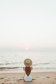 Giovane donna abbronzata che indossa un bellissimo costume da bagno bianco con un cappello di paglia è seduta e rilassante sulla spiaggia tropicale con sabbia bianca e sta guardando il tramonto e il mare