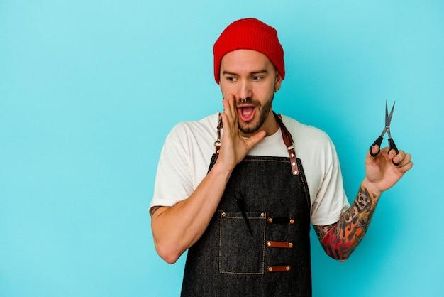Il giovane barbiere tatuato isolato su sfondo blu sta dicendo una notizia segreta di frenata calda e sta guardando da parte