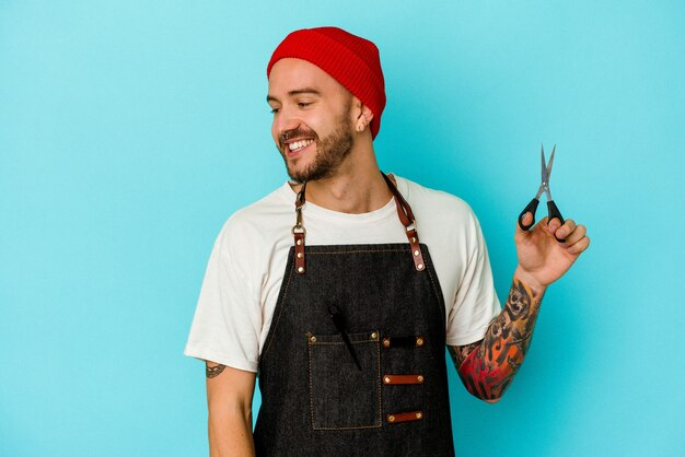 Uomo giovane barbiere tatuato isolato su sfondo blu guarda da parte sorridente, allegro e piacevole.