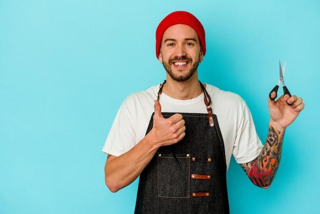 Giovane uomo tatuato del barbiere isolato sulla parete blu che sorride e che alza il pollice in su
