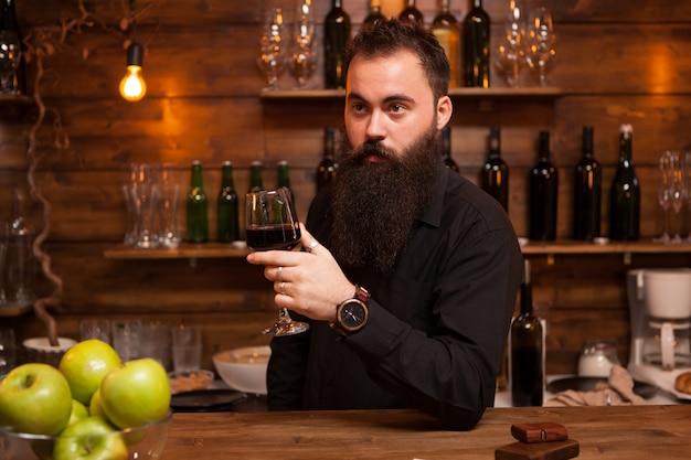 Giovane barista tatuato con una grande barba che assaggia un bicchiere di vino. pub alla moda.