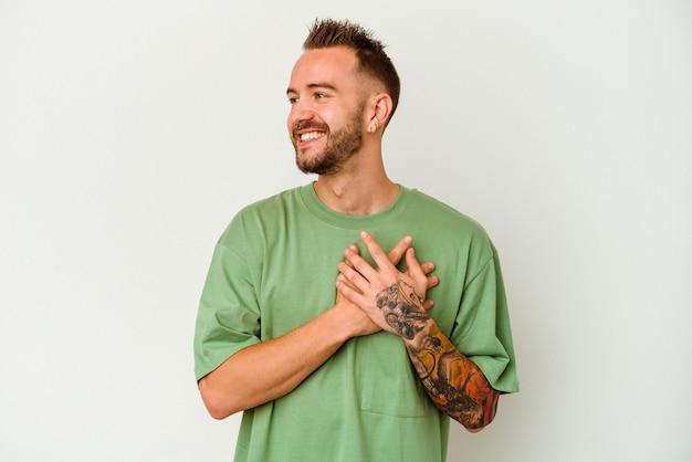 Giovane uomo caucasico tatuato isolato su sfondo bianco ridendo tenendo le mani sul cuore, il concetto di felicità.